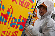 An activist carries a banner calling for the release of Fumiaki Hoshino who was arrested in 1975 for the alleged killing of a police officer during riots in Tokyo and sentenced to life imprisonment at a rally organized by Doro Chiba labour union to protest the outsourcing of what they consider essential safety and repair work and fight against rationalization of JR (Japan Railways) business. They also protested for the reinstatement of 1,047 national railway workers who lost their jobs in 1987. Shibuya, Tokyo, Japan Saturday, February 13th 2010