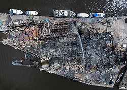 © Licensed to London News Pictures. 04/05/2021. London, UK. Fire fighters continue to damp down the remains of two boatyards on Platt's Eyot, an island on The River Thames in south west London after yesterday's blaze. It is being reported that a Dunkirk Little Ship 'The Lady Gay' was destroyed in the fire as it was on a slipway at the yard.  Photo credit: Peter Macdiarmid/LNP