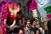 People carrying flags depicting the Extinction Rebellion logo listen to a speech during a protest against climate change in the middle of Oxford Circus on 15th April, 2019 in London, United Kingdom.  Extinction Rebellion have blocked five central London landmarks in protest against government inaction on climate change. (Photo by Jonatha Perugia/In Pictures via Getty Images).