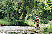 A father and daughter fly fishing on a small river for trout along the Oregon coast.