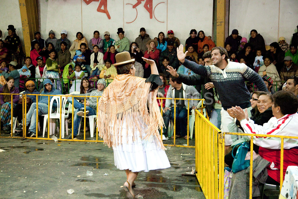 Female wrestler giving high fives 5s to male foreigners travellers in crowd. Lucha Libre wrestling origniated in Mexico, but is popular in other latin Amercian countries, including in La Paz / El Alto, Bolivia. Male and female fighters participate in the theatrical staged fights to an adoring crowd of locals and foreigners alike.