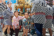Young children, helped by adults, carry a small palanquin through the streets during the Sanja Matsuri. Sanja Matsur (Three Shrine Festival), is an annual Shinto festival held in Tokyo. The earliest form of the festivals dates back to the 7th century CE and is held in honor of Hinokuma Hamanari, Hinokuma Takenari and Hajino Nakatomo, the three men who established and founded Sensō-ji temple. Sanja Matsuri is held on the third weekend of every May at Asakusa Shrine. Its  parades revolve around three mikoshi (three portable shrines referenced in the festival's name), as well as traditional music and dancing.