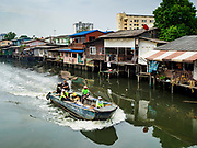 """22 MARCH 2018 - BANGKOK, THAILAND: City garbage haulers in a boat go past homes on Khlong Lat Phrao. Bangkok officials are evicting about 1,000 families who have set up homes along Khlong  Lat Phrao in Bangkok, the city says they are """"encroaching"""" on the khlong. Although some of the families have been living along the khlong (Thai for """"canal"""") for generations, they don't have title to the property, and the city considers them squatters. The city says the residents are being evicted so the city can build new embankments to control flooding. Most of the residents have agreed to leave, but negotiations over compensation are continuing for residents who can't afford to move.      PHOTO BY JACK KURTZ"""