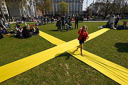 """© Licensed to London News Pictures. 15/04/2019. LONDON, UK.  A child runs across a giant X marked out on the park at Marble Arch as people surround Marble Arch taking part in """"London: International Rebellion"""", a protest organised by Extinction Rebellion, demanding that governments take action against climate change.  Marble Arch, Oxford Circus, Piccadilly Circus, Waterloo Bridge and Parliament Square have been blocked by activists.  According to the organiser, similar protests are taking place in 80 other cities around the world.  Photo credit: Stephen Chung/LNP"""