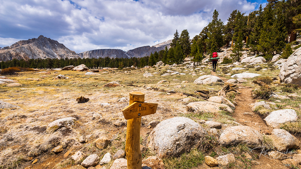 Backpacker and trail sign in the Cottonwood Lakes Basin, John Muir Wilderness, California USA
