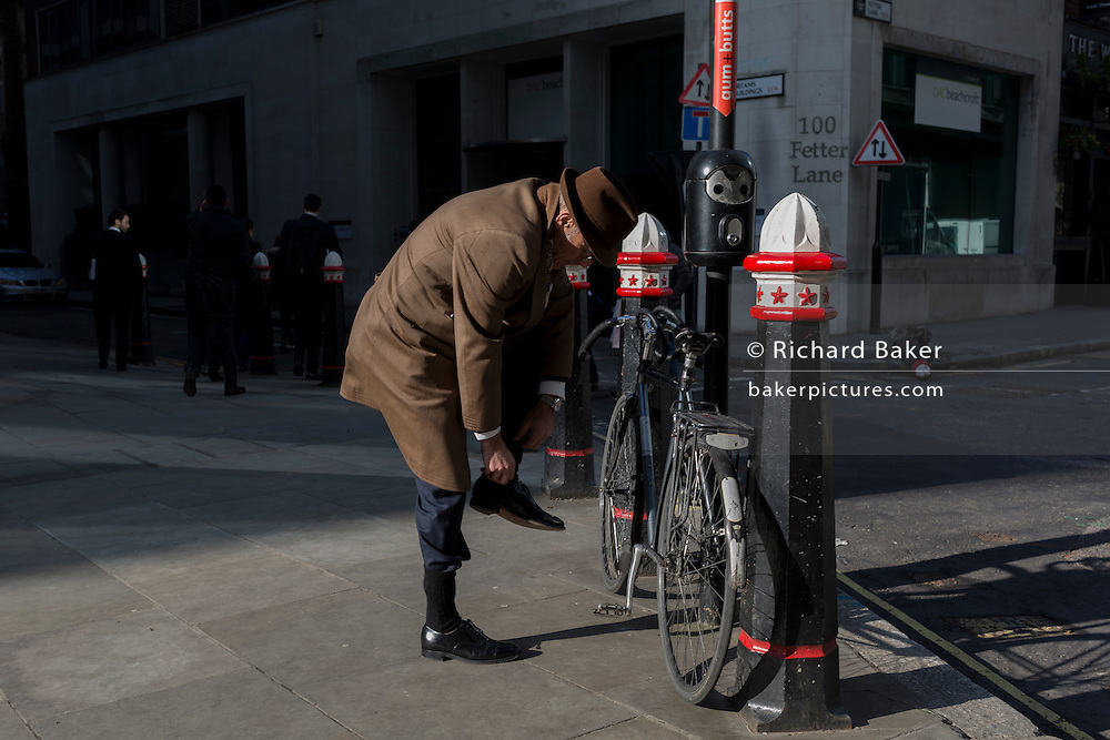 A cyclist tucks socks in trousers before riding away down Fetter Lane, on 13th February 2017, in the City of London, United Kingdom.