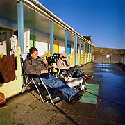 A couple and their dog sit outside Bakers Chalets (beach huts), Filey, North Yorkshire, UK