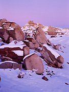 Snow capping boulders of Sonsela Sandstone with badlands and hoodoos of Blue Mesa, pastel light of dusk, Chinle Formation, Petrified Forest National Park, Arizona.