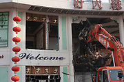 Old China comes crashing down in Shanghai, China. A Daewoo digger knocks down one of the last remaining old buildings in the heart of Pudong, Shanghais financial district. The Welcome sign and Chinese lanterns in marked contrast to the ever present destruction of old Shanghai around the city.