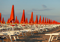 THEMENBILD - orange Sonnenschirme und leere Liegestühle in einer Reihe an einem Sandstrand, aufgenommen am 16. Juni 2018, Lignano Sabbiadoro, Österreich // orange umbrellas and empty beach chairs in a row on a sandy beach on a sandy beach on 2018/06/16, Lignano Sabbiadoro, Austria. EXPA Pictures © 2018, PhotoCredit: EXPA/ Stefanie Oberhauser