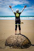 Tourist celebrating at the Moeraki boulders, Moeraki, Otago, South Island, New Zealand