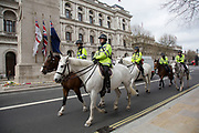 Mounted police pass the Cenotaph on Whitehall in London, England, United Kingdom.