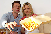 couple sitting on sofa eating pizza and chips, offering chips towards camera, fast food, tv dinners<br />
