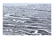 a sandur, an outwash plain, of glacial sediments deposited by meltwater in coastal Iceland with light layer of snow creating meandering patterns