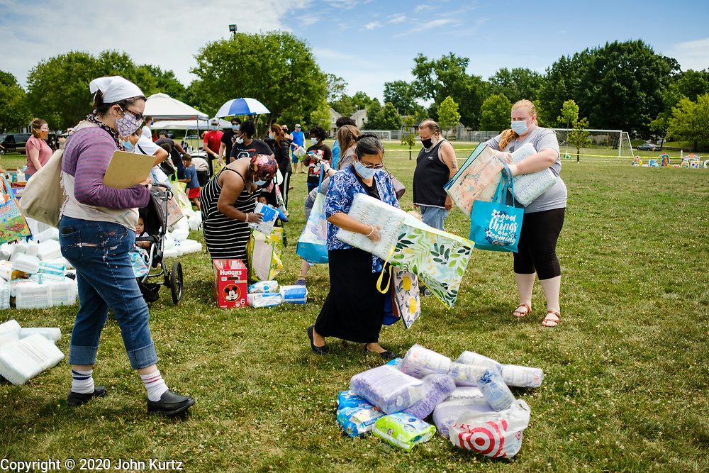 """19 JULY 2020 - DES MOINES, IOWA: A woman picks up diapers during """"A Celebration of Black Motherhood"""" in Des Moines Sunday. The event was organized by the Supply Hive and Black Lives Matter. Items were donated by members of the community and redistributed to at risk families. They distributed diapers, sanitary products, clothes, books, and toys. They had enough material to help 200 families.          PHOTO BY JACK KURTZ"""