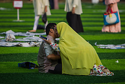 February 14, 2013 - Central Jakarta, Jakarta, Indonesia - Women kiss her husband after Eid Al-Fitr prayer on plastic grass at futsal stadium on June 15, 2018 in Jakarta, Indonesia. Muslims around the world are celebrating Eid al-Fitr, the three day festival marking the end of the Muslim holy month of Ramadan, it will be observed on 15th or 16th of June depending on the lunar calendar. Eid al-Fitr is one of the two major holidays in Islam. (Credit Image: © Afriadi Hikmal via ZUMA Wire)
