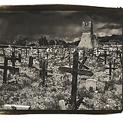 The old cemetery, surrounding the original church of San Geronimo, is filled with old graves. The graveyard is in sunlight while the dark sky looming in the background is a precursor to a thunderstorm.