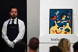 © Licensed to London News Pictures. 19/06/2019. LONDON, UK. A technician presents ''Peinture (L'Air)'' by Joan Miró, (Est. £10,000,000 - 15,000,000) which sold for a hammer price of £10,400,000 at Sotheby's Impressionist & Modern art evening sale in New Bond Street. This is the first major evening sale to take place after Sotheby's agreed to a takeover by media and telecoms billionaire Patrick Drahi in a deal valued at $3.7bn (£2.9bn).  The big five global auction houses (Sotheby's, Christie's, Bonhams, Phillips and China Guardian Auctions) will now be held privately.  Francois Pinault, another French billionaire, owns Sotheby's traditional rival Christie's.   Photo credit: Stephen Chung/LNP