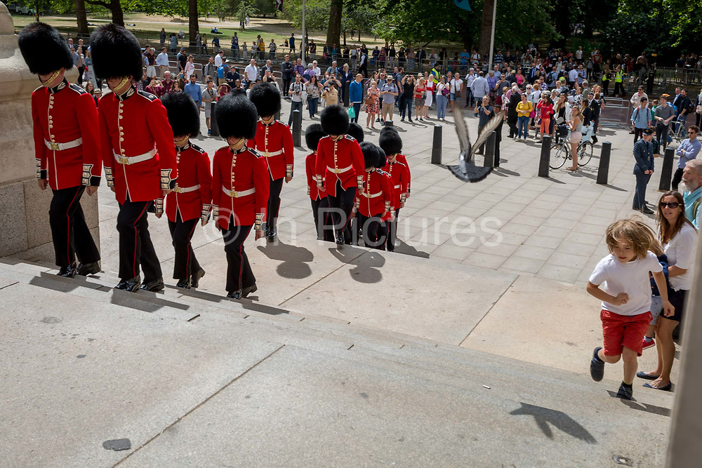 On the 100th anniversary of the Royal Air Force RAF and following a flypast of 100 aircraft formations representing Britains air defence history which flew over central London, guardsmen march up steps between the Foreign Office and the Churchills War Rooms, on 10th July 2018, in London, England.