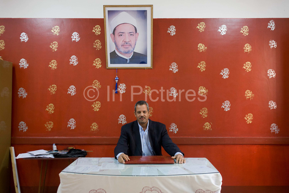 A portrait of the school headmaster beneath a picture of a Muslim cleric at the Islamic Koom al-Bourit Institute for Boys in the village of Qum (Koom), on the West Bank of Luxor, Nile Valley, Egypt. Islam in Egypt is the dominant religion in a country with around 80 million Muslims, comprising 94.7% of the population, as of 2010. Almost the entirety of Egypt's Muslims are Sunnis, with a small minority of Shia and Ahmadi Muslims. The latter, however, are not recognised by Egypt.