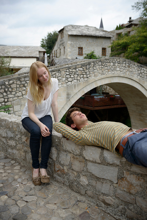 Two young adults, a woman from Finland and a man from Italy, relax in conversation beside the historic Crooked Bridge (Kriva Cuprija) in Mostar, Bosnia and Herzegovina. They had met earlier in the day, and would soon say goodbye.