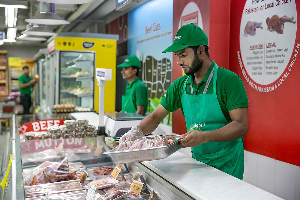 INDIVIDUAL(S) PHOTOGRAPHED: MD Halizul Haque. LOCATION: Agora, Uttara, Bangladesh. CAPTION: MD Halizul Haque organises cuts of meat at the meat counter at Agora in Uttara, Bangladesh.