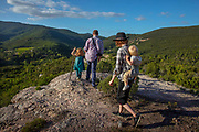 Family hiking to a lookout spot on a summers evening on a mountain 5th October 2019 in the village of Terme, France. Hiking is a powerful cardio workout that can lower the risk of heart disease and improve blood pressure and sugar levels sa well as boost bone density, since walking is a weight-bearing exercise.