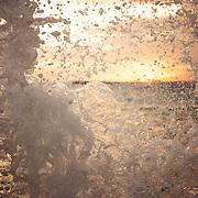 Spray and foam from waves crashing into seawalls shoot skyward under a sunset in Honolulu, Oahu, Hawaii.