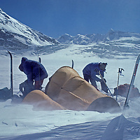 Ski Mountaineers break camp amidst blowing spindrift in the snowy Warwan Valley, en route from Ladakh to Kashmir during an expedition across India's Great Himalaya Range.