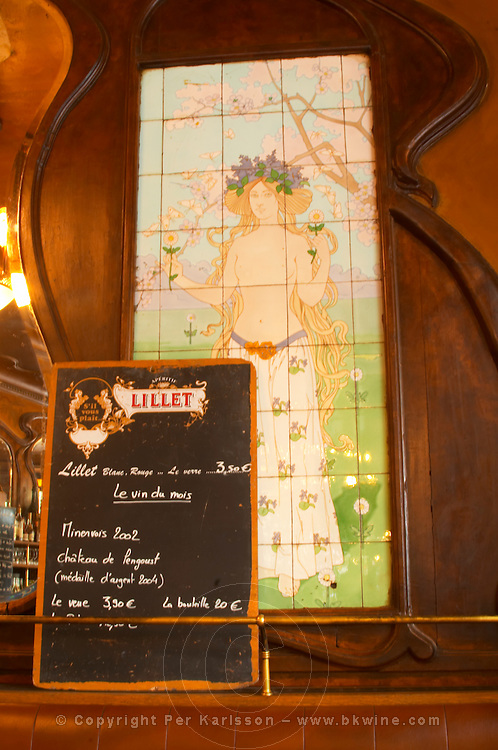 A closeup of the menu on a chalk black board blackboard chalkboard with Lillet written on it with this month's special offers on wine. On the wall a painting of a nymph, half naked young girl, on tiles, and wooden panelled walls The Bistrot du Peintre is an old fashioned Paris café cafe bar restaurant of art nouveau design with polished brass, mirrors and old signs