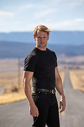 hot blond man standing in the middle of a long deserted road