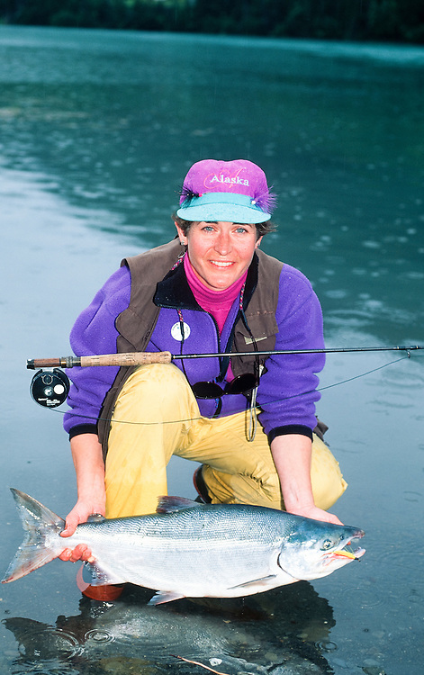 Alaska. Kenai Peninsula. Kenai River. A woman releasing a red salmon (Oncorhynchus nerka), sea run male. MR.