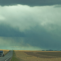 Trucks speed past wheat empty ranchland on U.S. Highway 287, north of Three Forks, Montana.