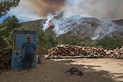 A man with his dog keep watches a wildfire, Friday May 31, 2013, near Castiac, California. Fourteen aircraft and more than 550 firefighter were deployed in a ground and air campaign against a brush fire that has blackened about 1,500 acres in sparsely populated San Francisquito Canyon in the Angeles National Forest northeast of Santa Clarita. The Powerhouse Fire, which broke out Thursday afternoon, was about 15 percent contained. The estimated date of full containment is Wednesday, June 5. (Photo by Ringo Chiu/PHOTOFORMULA.com)