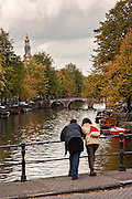 Couple looks at the canal along Prinsengracht with the Westerkerk tower during autumn in Amsterdam.