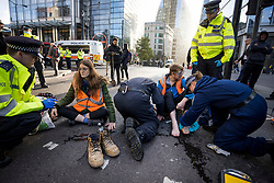 © Licensed to London News Pictures. 25/10/2021. London, UK. Insulate Britain climate change activist JOSHUA SMITH (right) being arrested after glueing his feet to the road in an attempt to block traffic on Bishopsgate in the City of London. The group have restarted their actions to block motorways and major roads causing disruption in the week before the COP26 climate meeting in Glasgow on 31/10/2021. Photo credit: Ben Cawthra/LNP