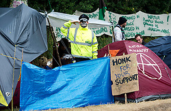 © London News Pictures. 17/08/2013. Balcombe, UK. Campaigners gather outside of the entrance to the Cuadrilla drilling site in Balcombe, West Sussex which has been earmarked for fracking. Cuadrilla has temporarily ceased drilling at the site under advice from the police after campaign group No Dash For Gas threatened a weekend of civil disobedience. Photo credit: Ben Cawthra/LNP