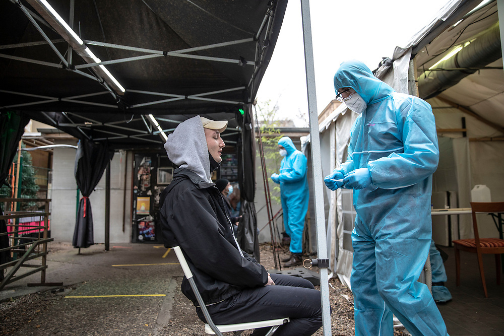 Medical personnel staff member explains about a covid antigen rapid swab tests to a person at a covid-19 test station outside the Kitkat night club in Berlin, Germany, December 13, 2020. Berlin's world famous KitKatClub has initiated a fast covid-19 tests operation in its premises People are able to set an online appointment and arrive to have a covid antigen rapid test swab test in what was reported by local media outlet as the lowest price in the German capital. The club itself is closed since early 2020 due to the health restrictions imposed on cultural venues in Germany.