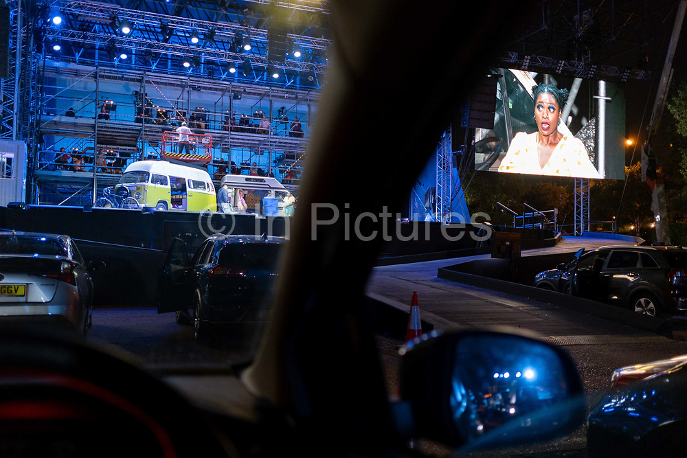 Seen from the driver's seat, British Soprano Nardus Williams plays Mimi in Puccini's La bohème, performed by English National Opera (ENO) as a drive-in (ENO Drive and Live) at Alexandra Palace, on 18th September 2020, in London, England. This is ENO's first public performance since the closure of their West End Colisseum home venue, because of the Coronavirus pandemic lockdown in March. This is Europe's first live drive-in opera production that audiences can safely experience from their cars and ENO's first public performance since the closure of their West End Colisseum home venue, because of the Coronavirus pandemic lockdown in March. As per the latest government advice. Each bubbled group consists of; 34 members of the ENO Orchestra, 20 ENO Chorus members and 8 principals. Each bubble has its own individual crew to oversee their rehearsals and performances.
