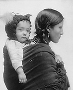Native American woman from the  Plains region, half-length portrait, facing right, with baby on her back.  20th century Twentieth century