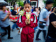 "01 MARCH 2018 - BANGKOK, THAILAND:    A nursing student from the Thai police hospital prays while people participate in a procession at Wat Pathum Wanaram in central Bangkok. Many people go to temples to perform merit-making activities on Makha Bucha Day, which marks four important events in Buddhism: 1,250 disciples came to see the Buddha without being summoned, all of them were Arhantas, or Enlightened Ones, and all were ordained by the Buddha himself. The Buddha gave those Arhantas the principles of Buddhism. In Thailand, this teaching has been dubbed the ""Heart of Buddhism.""    PHOTO BY JACK KURTZ"