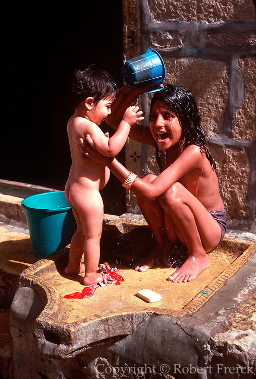 INDIA, RAJASTHAN Baby brother and sister bathing in the city of Jaisalmer