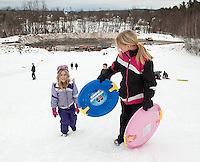 "Sandra Leonard carries her younger sister Stephanie's  ""snow spinner"" up to the top of the hill during Tuesday's sledding party hosted by Laconia Recreation at Memorial Field.   (Karen Bobotas/for the Laconia Daily Sun)"