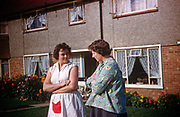 Two mothers and neighbours gossip with arms folded outside their houses on an Essex estate in the early nineteen sixties. Wearing aprons popular for working mums in this era of early 1960s, and one seemingly pregnant, the two women talk about families and children and their lives at the beginning of a new decade. This row of houses is in the Essex suburb of Westcliff, Southend and a proud gardener has grown a colourful bed of dahlias in the front. The picture was recorded on Kodachrome (Kodak) film in about 1961.