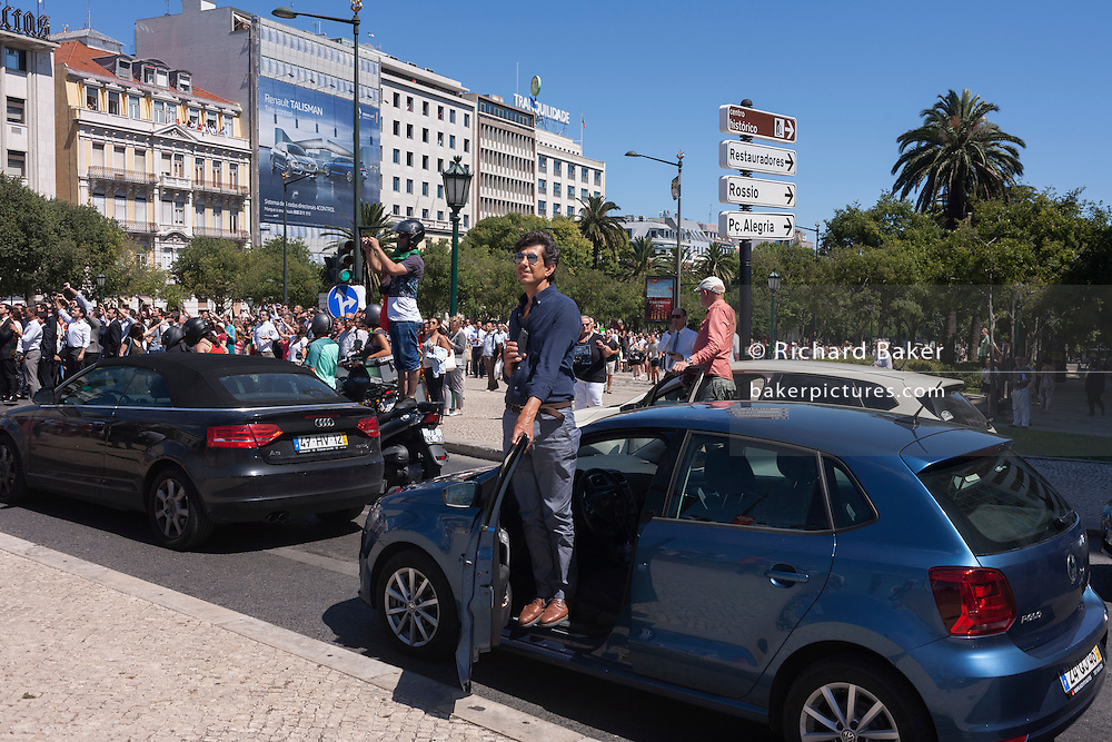 Portuguese drivers and riders, forced to stop their vehicles for the crowds, watch their national football team during their victory procession through the capital's streets, the day after the Euro 2016 final with France, on 11th July 2016, in Lisbon, Portugal. Standing higher to gain a better view in Praca Marques de Pombal in the largely corporate and banking district of the city, they take photos and cheer their favourite players, including the national hero/deity, Christiano Ronaldo. (Photo by Richard Baker / In Pictures via Getty Images)