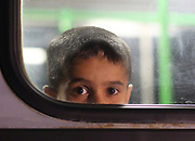 A young migrant boy at the window of a bus close to the Hungarian and Serbian border town of Roszke, Hungary, September 8 2015. The UN's humanitarian agencies are on the verge of bankruptcy and unable to meet the basic needs of millions of people because of the size of the refugee crisis in the Middle East, Africa and Europe, senior figures within the UN have told the media.