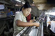 """25 FEBRUARY 2008 -- MAE SOT, TAK, THAILAND: Illegal Burmese workers in a hosiery factory in Mae Sot, Thailand. The factory owner allegedly bribes Thai officials not to raid his place. Workers here work seven days a week, 14 hours per day and make about $5 US per day. Their housing, which is provided by the factory owner, is in the factory compound. There are millions of Burmese migrant workers and refugees living in Thailand. Many live in refugee camps along the Thai-Burma (Myanmar) border, but most live in Thailand as illegal immigrants. They don't have papers and can not live, work or travel in Thailand but they do so """"under the radar"""" by either avoiding Thai officials or paying bribes to stay in the country. Most have fled political persecution in Burma but many are simply in search of a better life and greater economic opportunity.  Photo by Jack Kurtz"""