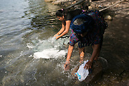 Silva and Abuelita wash the family's dirty laundry in Lake Atitlan. Much of the lake is polluted.