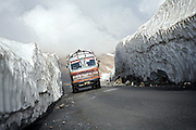 A truck is passing through a narrow and steep section of the Leh-Manali Highway.