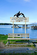 A sign decorated with an orca notes the Pacific Terminus of the Trans Canada Highway in Tofino, British Columbia